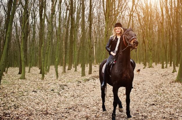 Joven rubia elegante montando a caballo en el bosque de otoño