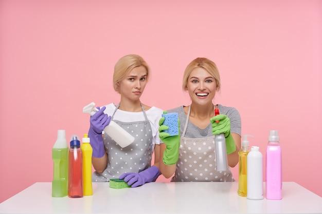 Joven rubia encantadora amas de casa con guantes de goma mientras se prepara para la limpieza de primavera