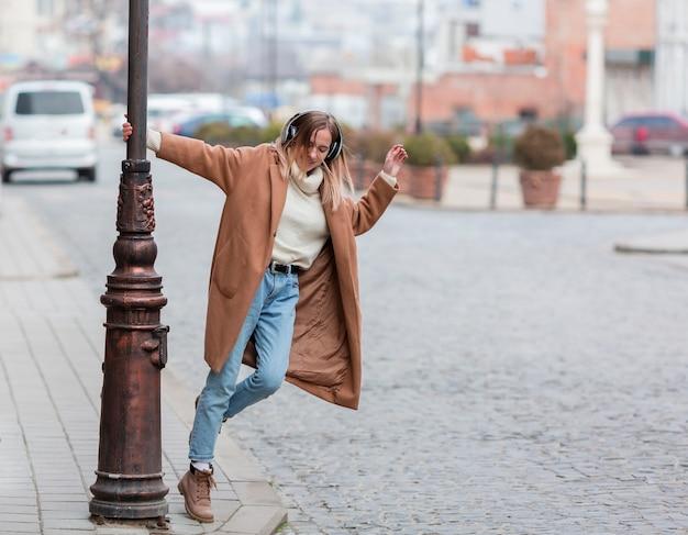 Joven rubia escuchando música con auriculares en la ciudad