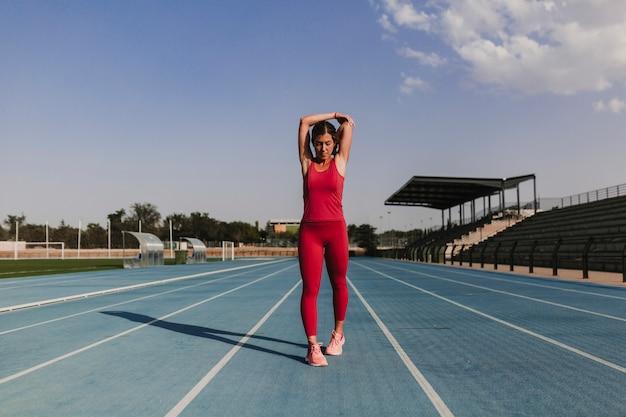 Joven rubia fitness mujer corredor estirando los brazos en la pista azul del estadio al atardecer. concepto de deporte y estilo de vida saludable