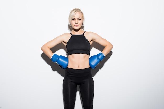 Joven rubia con guantes de boxeo azules preparada para ganar en blanco