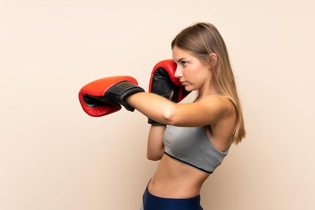 Joven rubia con guantes de boxeo sobre pared aislada