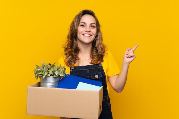 Joven rubia haciendo un movimiento mientras levanta una caja llena de cosas que apuntan a un lado para presentar un producto