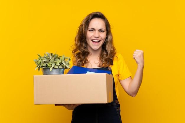 Joven rubia haciendo un movimiento mientras recogía una caja llena de cosas celebrando una victoria