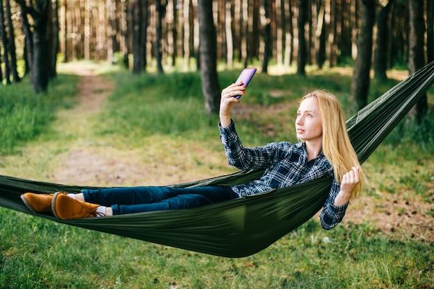 Joven rubia hermosa chica relajante en hamaca y haciendo selfie en bosque de verano