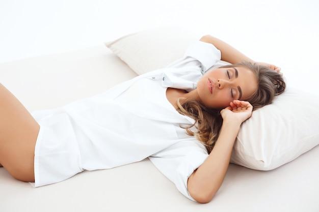 Joven rubia hermosa mujer durmiendo en la cama temprano en la mañana.