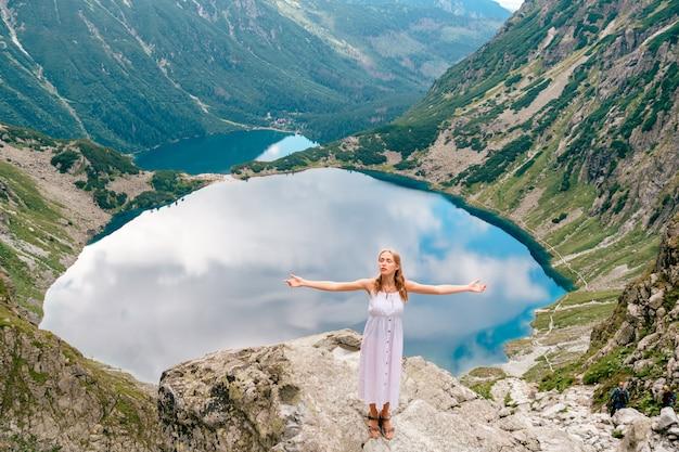 Joven rubia hermosa en vestido blanco de pie en piedra en las montañas con las manos separadas y hermoso lago detrás.