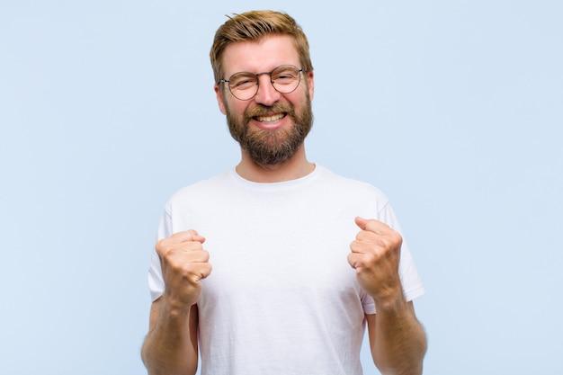 Joven rubia hombre adulto gritando triunfante, riendo y sintiéndose feliz y emocionado mientras celebra el éxito