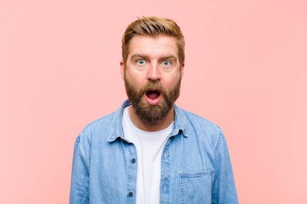 Joven rubia hombre adulto mirando muy sorprendido o sorprendido, mirando con la boca abierta diciendo wow