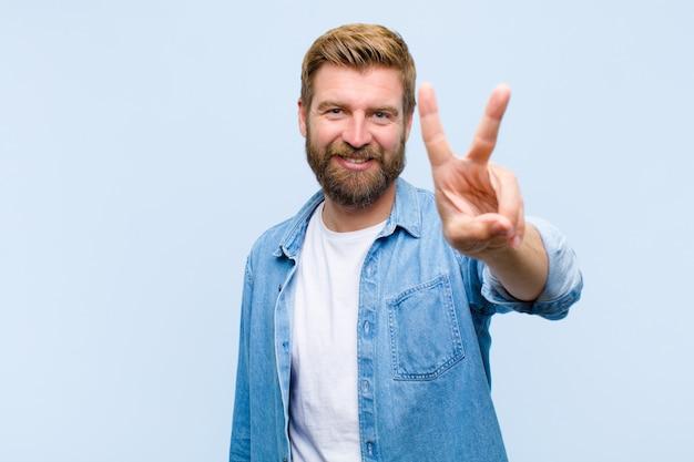Joven rubia hombre adulto sonriendo y mirando amigable, mostrando el número dos o segundo con la mano hacia adelante, contando hacia atrás