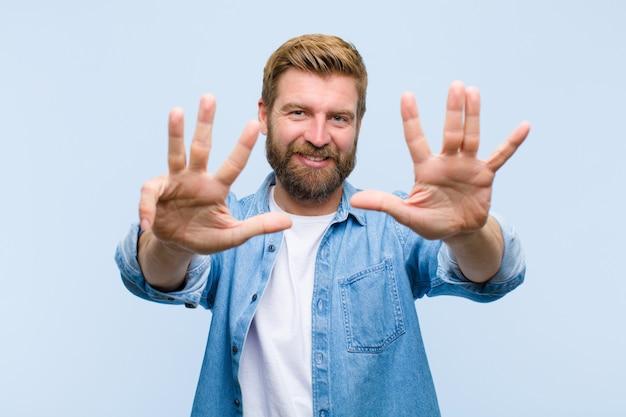 Joven rubia hombre adulto sonriendo y mirando amigable, mostrando el número nueve o noveno con la mano hacia adelante, cuenta atrás