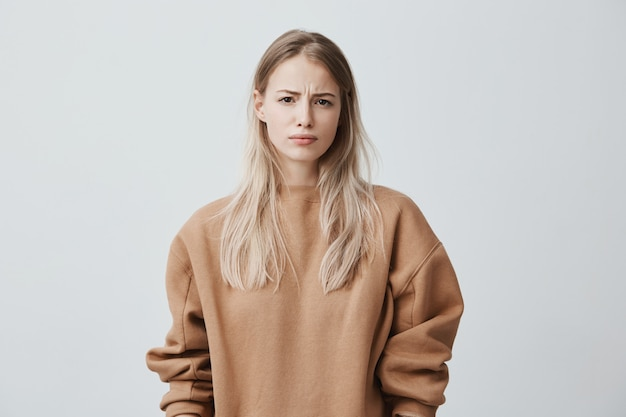 Joven rubia insatisfecha con suéter de manga larga con el ceño fruncido, mirando enojado
