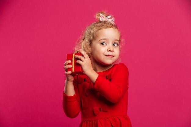 Joven rubia intrigada en vestido rojo con caja de regalo