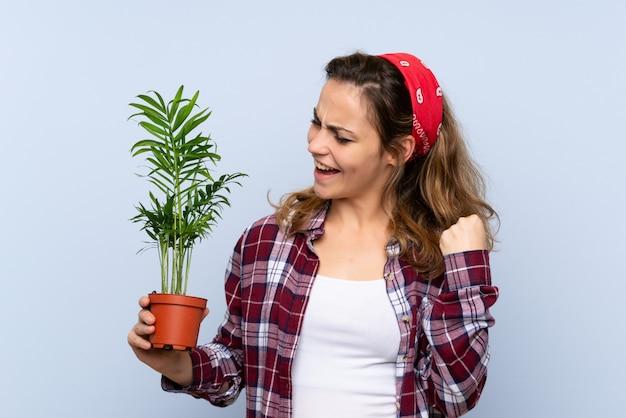 Joven rubia jardinero chica sosteniendo una planta celebrando una victoria