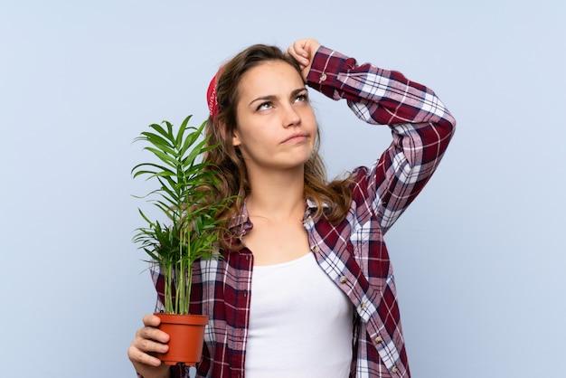 Joven rubia jardinero chica sosteniendo una planta con dudas y con expresión de la cara confusa