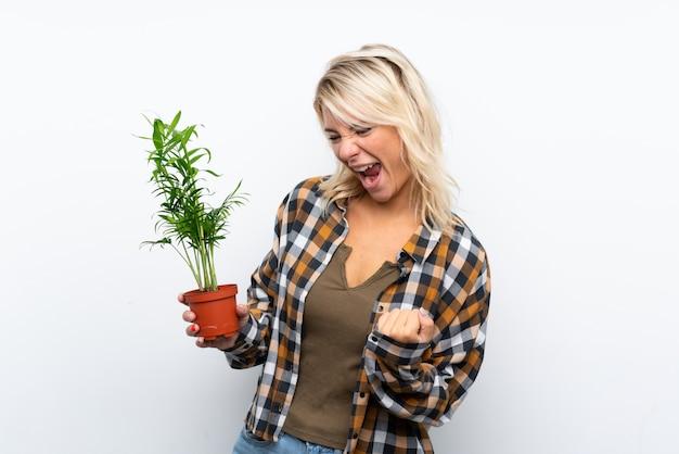 Joven rubia jardinero mujer sosteniendo una planta sobre pared blanca aislada celebrando una victoria