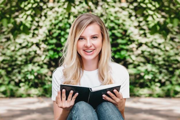 Joven rubia lee un libro y se ríe en un parque sobre un fondo de árboles y arbustos