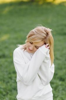 Joven rubia lleva una sudadera con capucha blanca sonriendo y caminando en el bosque