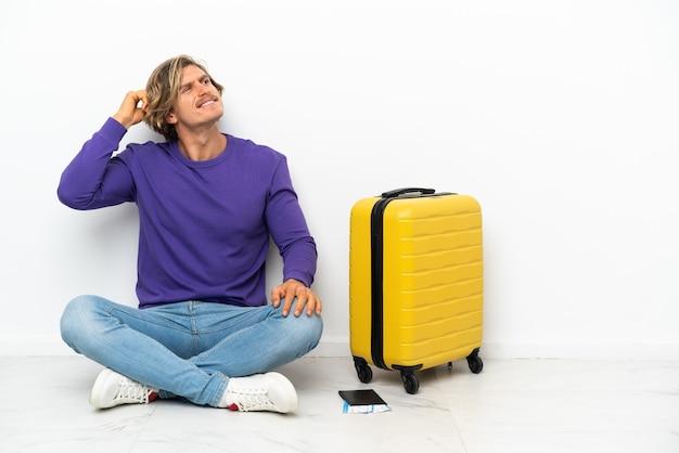Joven rubia con maleta sentada en el suelo con dudas y con expresión de la cara confusa