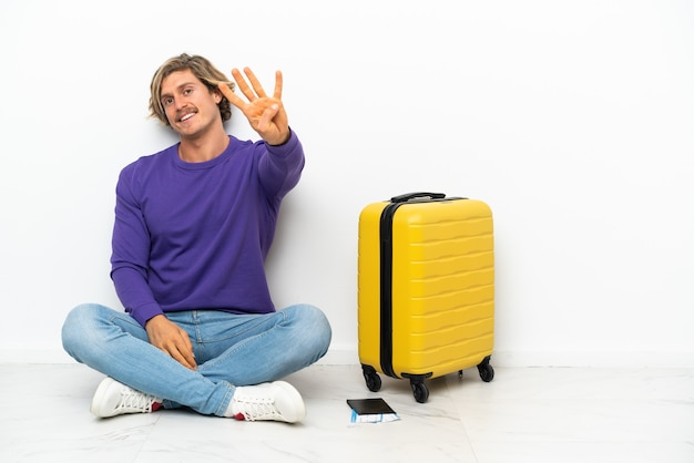 Joven rubia con maleta sentada en el suelo feliz y contando cuatro con los dedos