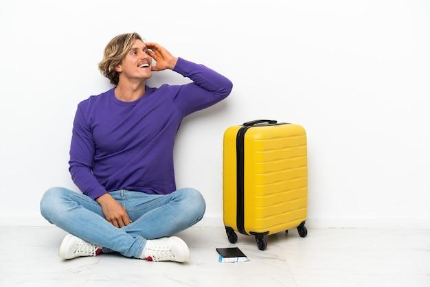 Joven rubia con maleta sentada en el suelo se ha dado cuenta de algo y tiene la intención de la solución