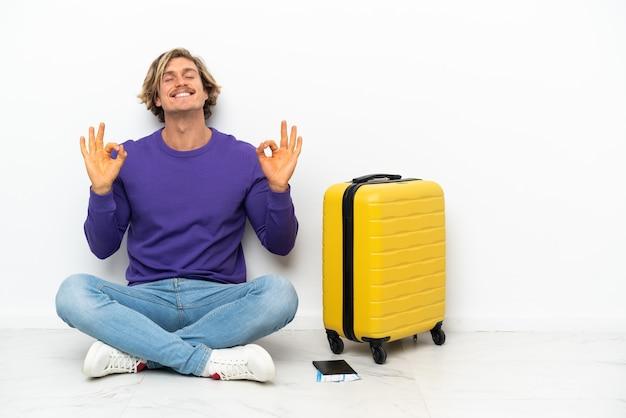 Joven rubia con maleta sentada en el suelo en pose zen