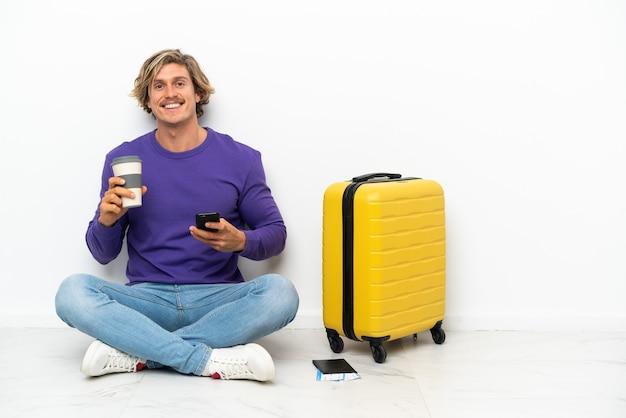 Joven rubia con maleta sentada en el suelo sosteniendo café