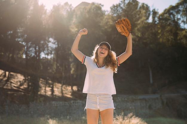 Joven rubia con las manos levantadas y el guante de béisbol en el fondo de la naturaleza