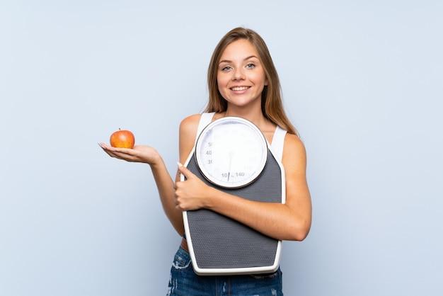 Joven rubia con máquina de pesaje y con una manzana sobre pared blanca azul aislada