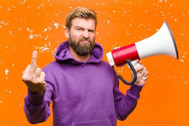 Joven rubia con un megáfono vistiendo una sudadera con capucha púrpura contra la pared naranja dañada