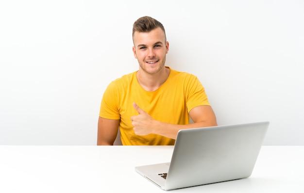 Joven rubia en una mesa con un portátil dando un gesto de pulgares arriba
