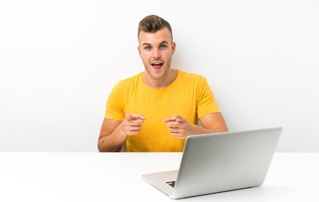 Joven rubia en una mesa con un portátil te señala con el dedo