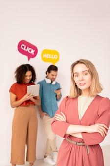 Joven rubia mujer de brazos cruzados en ropa casual de pie delante de la cámara en el fondo de sus amigos comunicándose en las redes sociales