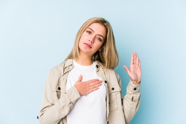 Joven rubia mujer caucásica aislada tomando un juramento, poniendo la mano en el pecho.