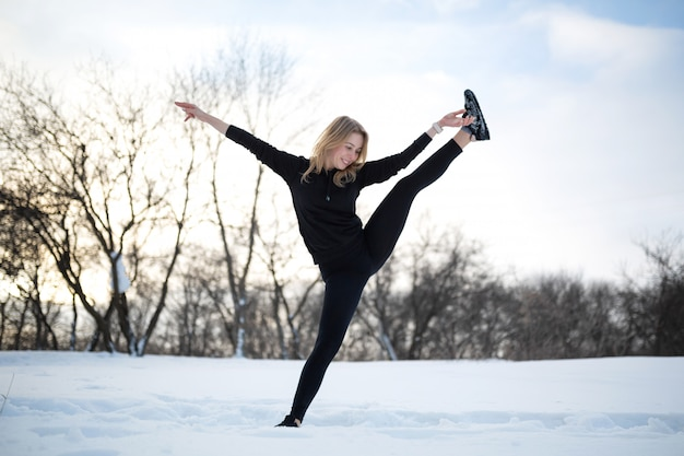 Joven rubia mujer caucásica en polainas estirando ejercicio al aire libre en bosque nevado