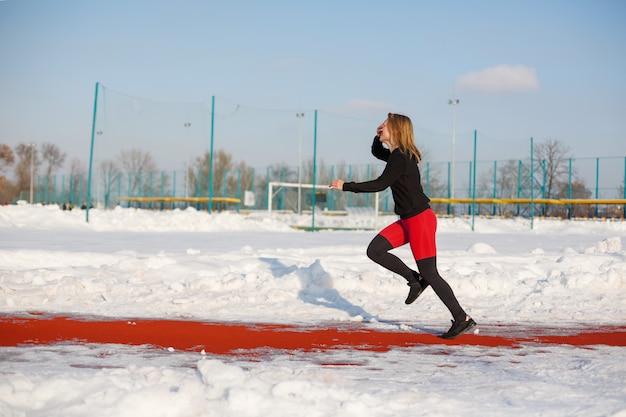 Joven rubia mujer caucásica en polainas violetas ejercicio de estiramiento en una pista roja en un estadio nevado, en forma y estilo de vida deportivo
