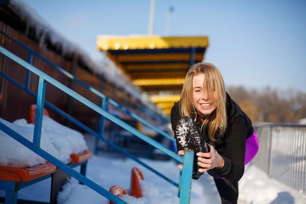 Joven rubia mujer caucásica en polainas violetas estirando ejercicio en tribuna en un estadio nevado, en forma y estilo de vida deportivo