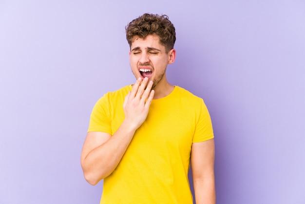 Joven rubia de pelo rizado hombre bostezando mostrando un gesto cansado cubriendo la boca con la mano