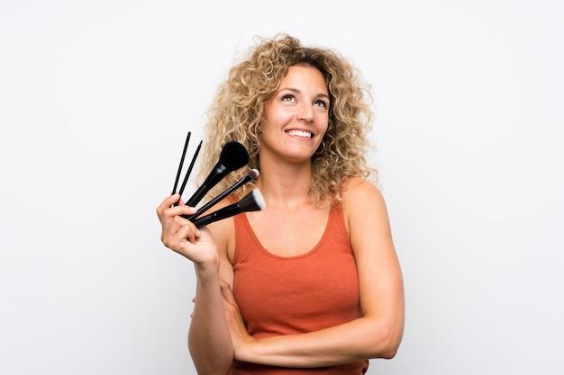 Joven rubia con el pelo rizado sosteniendo una gran cantidad de pincel de maquillaje mirando hacia arriba mientras sonríe