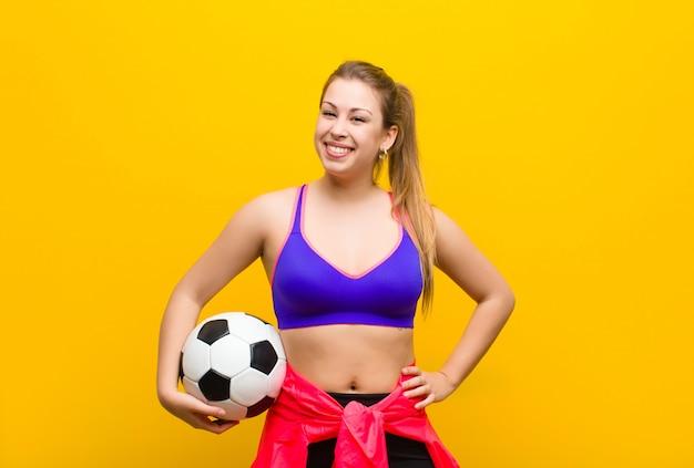 Joven rubia con una pelota de fútbol. concepto deportivo