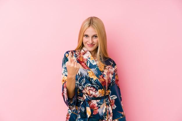 Joven rubia con un pijama de kimono apuntando con el dedo hacia ti como si invitara a acercarse.