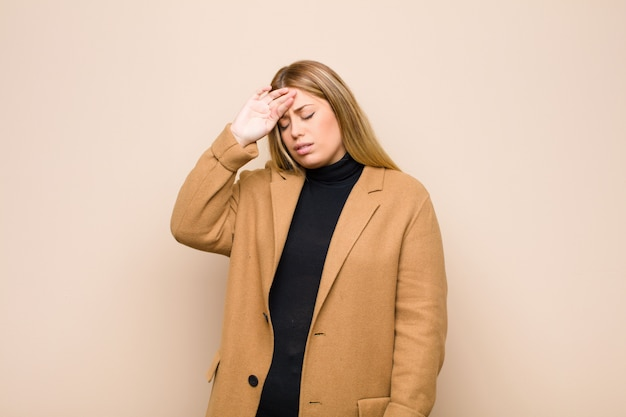 Joven rubia que parece estresada, cansada y frustrada, secándose el sudor de la frente, sintiéndose desesperada y agotada por la pared