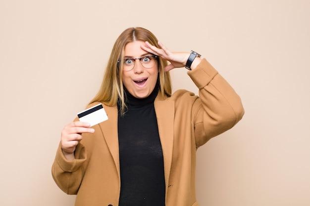 Joven rubia que parece feliz, asombrada y sorprendida, sonriendo y dándose cuenta de una increíble e increíble buena noticia con una tarjeta de crédito