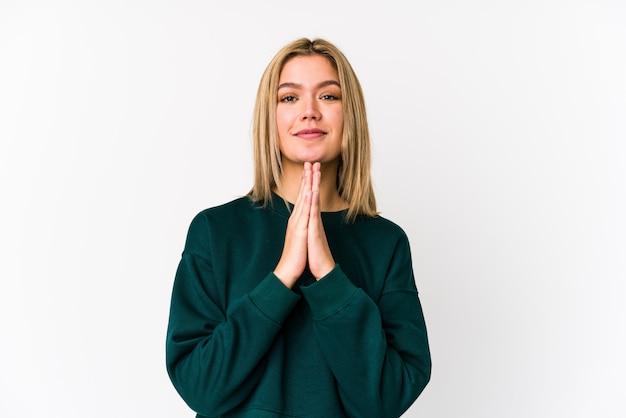 Joven rubia rezando, mostrando devoción, persona religiosa en busca de inspiración divina