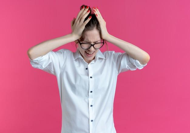 Joven rubia rusa dolorida con gafas pone las manos en la cabeza mirando hacia abajo aislado en el espacio rosa con espacio de copia