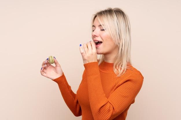 Joven rubia rusa sobre pared aislada sosteniendo coloridos macarons franceses y comiéndolo
