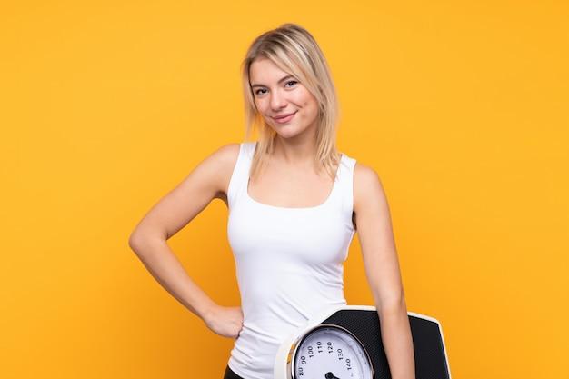 Joven rubia rusa sobre pared amarilla aislada con los brazos en la cadera y sosteniendo la máquina de pesaje