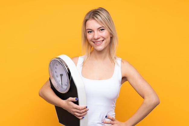 Joven rubia rusa sobre pared amarilla aislada con máquina de pesaje