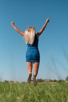 Joven rubia saltando mientras sostiene los brazos en el aire