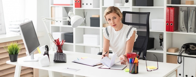 Una joven rubia está sentada en el escritorio de una computadora en la oficina, sosteniendo un lápiz en la mano y trabajando con documentos.